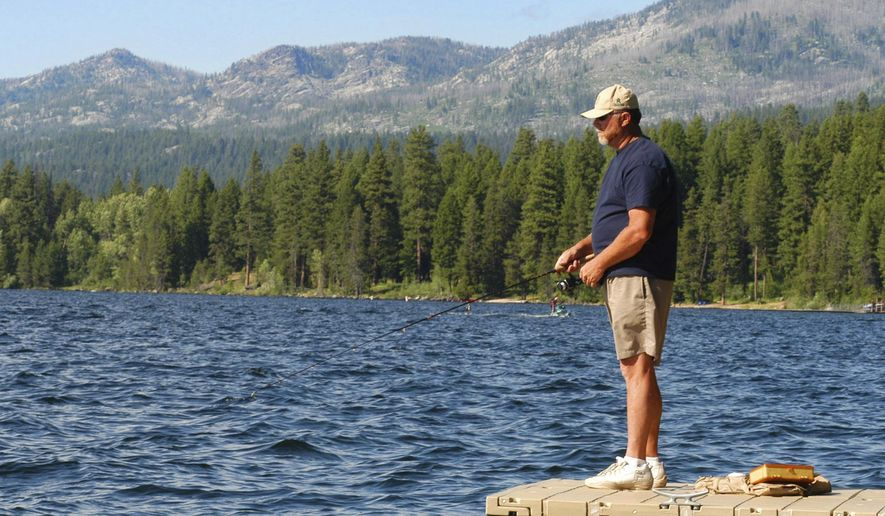 FILE - In this July 7, 2004, file photo, Dennis Rogers, of Corona, Calif., fishes off a dock at Ponderosa Park in McCall, Idaho, while vacationing. A private investment firm's proposal to swap private timberland in northern Idaho for up to 28,000 acres of public state land in and around the tourist destination of McCall that is also a popular area for vacation homes is facing opposition from local governments, environmental groups and private citizens. Trident Holdings LLC pitched the plan Tuesday, Nov. 17, 2020, to Republican Gov. Brad Little and four other statewide-elected members of the Idaho Land Board. (AP Photo/Matt Cilley, File)