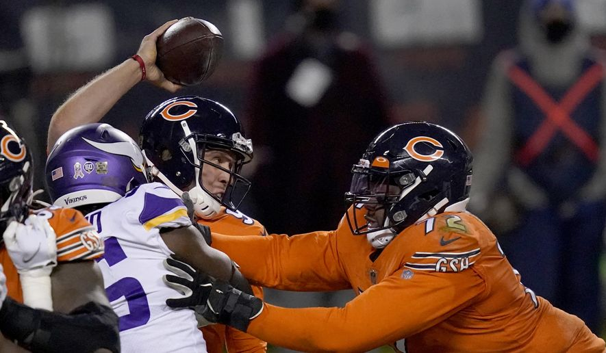 Chicago Bears quarterback Nick Foles tries to throw under pressure from Minnesota Vikings defensive end Ifeadi Odenigbo, left, as Bears offensive tackle Charles Leno Jr., right, pushes Odenigbo during the second half of an NFL football game Monday, Nov. 16, 2020, in Chicago. Foles was injured on the play and left the game. (AP Photo/Charles Rex Arbogast) **FILE**