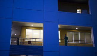 A hospital worker takes a break on an outdoor walkway as the day shift comes to an end and night falls upon the La Timone hospital in Marseille, southern France, Thursday, Nov. 12, 2020. France is more than two weeks into its second coronavirus lockdown, and intensive care wards have been over 95% capacity for more than 10 days now. Associated Press journalists spent 24 hours with the intensive care team at La Timone, southern France's largest hospital, as they struggled to keep even one bed open for the influx of patients to come. (AP Photo/Daniel Cole)