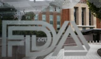 FILE - This Thursday, Aug. 2, 2018, file photo shows the U.S. Food and Drug Administration building behind FDA logos at a bus stop on the agency's campus in Silver Spring, Md. FDA officials on Tuesday, Nov. 17, 2020, allowed emergency use of the first rapid coronavirus test that can be performed and developed entirely at home. (AP Photo/Jacquelyn Martin, File)