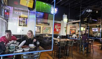 Cecelia Brockett, left, and Courtney Barefoot enjoy a lunch at the Winking Lizard Tavern, Monday, Nov. 16, 2020, in Beachwood, Ohio. Ohio Governor Mike DeWine issued a new health warning Sunday to limit mass gatherings. (AP Photo/Tony Dejak)