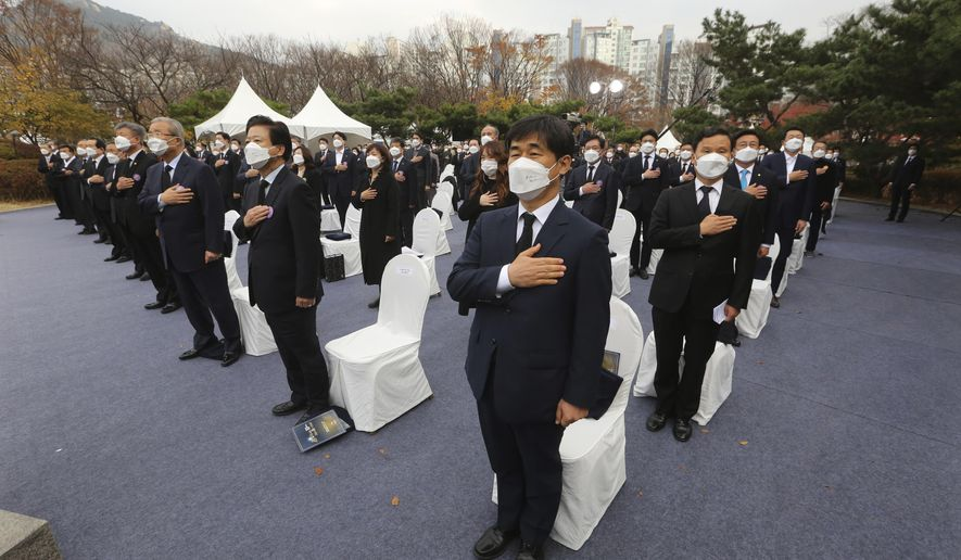 Attendees wearing face masks to help curb the spread of the coronavirus salute while maintaining social distancing during a ceremony to mark the 81st anniversary of the Memorial Day for Martyred Ancestors in Seoul, South Korea, Tuesday, Nov. 17, 2020. (AP Photo/Ahn Young-joon)