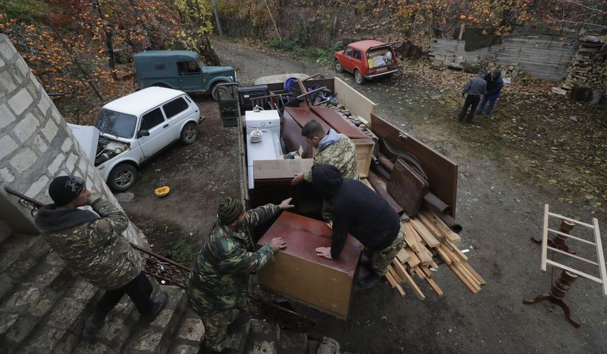 Ethnic Armenians load a truck as they prepare to leave their home in the village of Maraga, in the Martakert area, in the separatist region of Nagorno-Karabakh, Wednesday, Nov. 18, 2020. A Russia-brokered cease-fire to halt six weeks of fighting over Nagorno-Karabakh stipulated that Armenia turn over control of some areas it holds outside the separatist territory's borders to Azerbaijan. Armenians are forced to leave their homes before the region is handed over to control by Azerbaijani forces. (AP Photo/Sergei Grits)