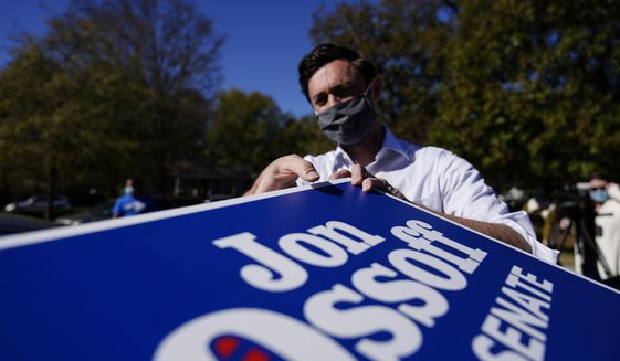 Georgia Democratic candidate for U.S. Senate Jon Ossoff grabs signs to give out during a drive-through yard sign pick-up event on Wednesday, Nov. 18, 2020, in Marietta, Ga. Ossoff and Republican candidate for Senate Sen. David Perdue are in a runoff election for the Senate seat. (AP Photo/Brynn Anderson)
