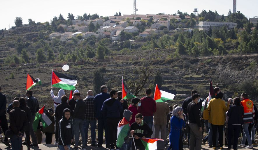 Palestinians protest against expected visit of the US Secretary of State Mike Pompeo to the Jewish settlement of Psagot near the West Bank city of Al-Bireh, Wednesday, Nov. 18, 2020.Secretary of State Mike Pompeo's expected tour of a West Bank winery this week will be the first time a top U.S. diplomat has visited an Israeli settlement, a parting gift from an administration that has taken unprecedented steps to support Israel's claims to war-won territory. (AP Photo/Majdi Mohammed)