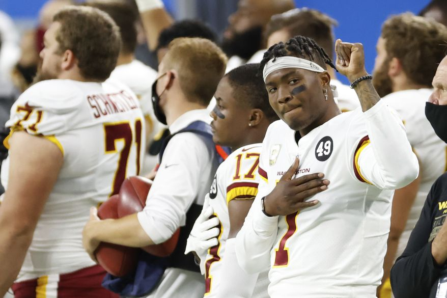 Washington Football Team quarterback Dwayne Haskins (7) raise a fist during the national anthem during an NFL football game against the Detroit Lions, Sunday, Nov. 15, 2020, in Detroit. (AP Photo/Rick Osentoski)