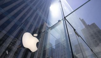 """FILE - In this June 16, 2020, file photo, the sun is reflected on Apple's Fifth Avenue store in New York. Apple will cut its app store fee in half from 30% to 15% for most developers beginning Jan. 1, the biggest change in its commission rate since the app store began in 2008. The fee reduction will apply to developers who made up to $1 million from the app store in 2020, which is the """"vast majority"""" of developers in the store, Apple said. (AP Photo/Mark Lennihan, File)"""