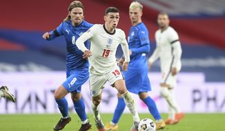 England's Phil Foden, center, and Iceland's Birkir Bjarnason challenge for the ball during the UEFA Nations League soccer match between England and Iceland at Wembley stadium in London, Wednesday, Nov. 18, 2020. (Michael Regan/Pool via AP)
