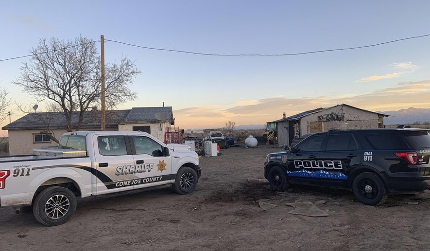In this photo released by the Colorado Bureau of Investigation, law enforcement vehicles are parked at on one two properties where skeletal remains were found about 20 miles (32 kilometers) south-southeast of Alamosa, Colo. on Wednesday, Nov. 18, 2020. Authorities in southern Colorado said Wednesday they are searching for a man in connection with the discovery of human remains belonging to three people near a rural hamlet. The Colorado Bureau of Investigation and local police agencies identified the suspect as 26-year-old Adre Jordan Baroz. (Colorado Bureau of Investigation via AP)