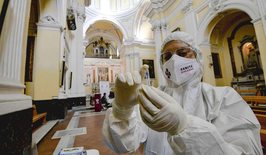 """A medical operator prepares to perform COVID-19 test swabs in the Church of San Severo Outside the Walls, in the heart of Naples, Italy, Wednesday, Nov. 18, 2020. An initiative of """"Sanita' Diritti Salute"""" association and the San Gennaro Foundation, aimed at helping those who cannot afford the cost of a private test, also allows, in the best tradition of Naples, those who want to pay 18 euros for a """"suspended swab"""", to be taken by somebody else, exactly as it happens for the famous Neapolitan """"suspended coffee"""". (Alessandro Pone /LaPresse via AP)"""