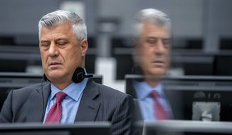 Hashim Thaci who resigned as Kosovo's president to face charges including murder, torture and persecution, and his attorney David Hooper, left, make their first courtroom appearance before a judge at the Kosovo Specialist Chambers court in The Hague, Netherlands, Monday, Nov. 9, 2020. An international prosecutor has indicted Thaci on 10 charges of crimes against humanity and war crimes for his leadership of fighters with the Kosovo Liberation Army who are accused of illegally imprisoning, abusing and murdering captured opponents and perceived traitors during the war. (Jerry Lampen via AP Photo, Pool)