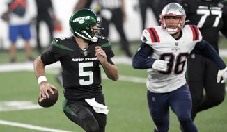 New York Jets quarterback Joe Flacco, left, looks to throw during the first half of an NFL football game against the New England Patriots, Monday, Nov. 9, 2020, in East Rutherford, N.J. (AP Photo/Bill Kostroun)