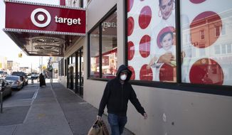 FILE - In this April 6, 2020 file photo, a customer wearing a mask carries his purchases as he leaves a Target store during the coronavirus pandemic, in the Brooklyn borough of New York. Target is the latest big U.S. retailer to show that it's prospering during the pandemic. The Minneapolis company reported Wednesday, Nov. 18 that its online sales surged 155% in the three months that ended Oct. 31. (AP Photo/Mark Lennihan, File)