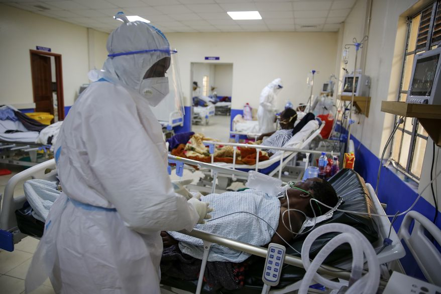 Medical workers attend to coronavirus patients in the intensive care unit of an isolation and treatment center for those with COVID-19 in Machakos, south of the capital Nairobi, in Kenya Tuesday, Nov. 3, 2020. As Africa is poised to surpass 2 million confirmed coronavirus cases it is Kenya's turn to worry the continent with a second surge in infections well under way. (AP Photo/Brian Inganga)