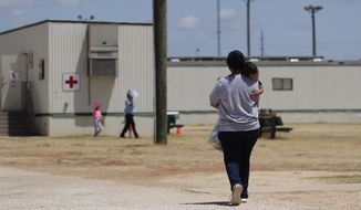 In this Aug. 23, 2019, photo, immigrants seeking asylum walk at the ICE South Texas Family Residential Center, in Dilley, Texas. A federal judge on Wednesday, Nov. 18, 2020, ordered the Trump administration to stop expelling immigrant children who cross the southern border alone, halting a policy that has resulted in thousands of rapid deportations of minors during the coronavirus pandemic. (AP Photo/Eric Gay) **FILE**