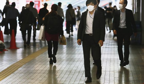 People wearing face masks to help curb the spread of the coronavirus walk underpass in Tokyo, Wednesday, Nov. 18, 2020. (AP Photo/Koji Sasahara)