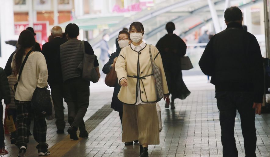 People wearing face masks to help curb the spread of the coronavirus walk underpass in Tokyo, Wednesday, Nov. 18, 2020. (AP Photo/Koji Sasahara)