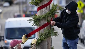 Workers attach holiday decorations to a utility pole in Dock Square, in advance of the holiday shopping season, Wednesday, Nov. 18, 2020, in Kennebunkport, Maine. (AP Photo/Robert F. Bukaty)