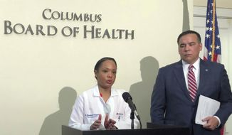 FILE - In this March 13, 2020 file photo, Dr. Mysheika Roberts, Columbus public health commissioner, speaks at a news conference, in Columbus, Ohio. Columbus Mayor Andrew Ginther, right, listens. Residents of Ohio's capital city and the surrounding county should stay at home as much as possible and not have guests inside their homes, including on Thanksgiving Day, according to an advisory stay-at-home order issued Wednesday, Nov. 18, 2020, by public health directors. (AP Photo/Andrew Welsh-Huggins, File)