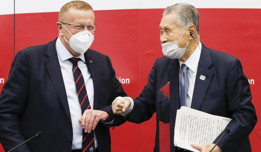 Yoshiro Mori, president of the Tokyo 2020 organizing committee, right, greets John Coates, chairman of the Coordination Commission for the Tokyo 2020 Olympics, during a press conference in Tokyo,  Wednesday, Nov. 18, 2020. (Rodrigo Reyes Marin/Pool Photo via AP)