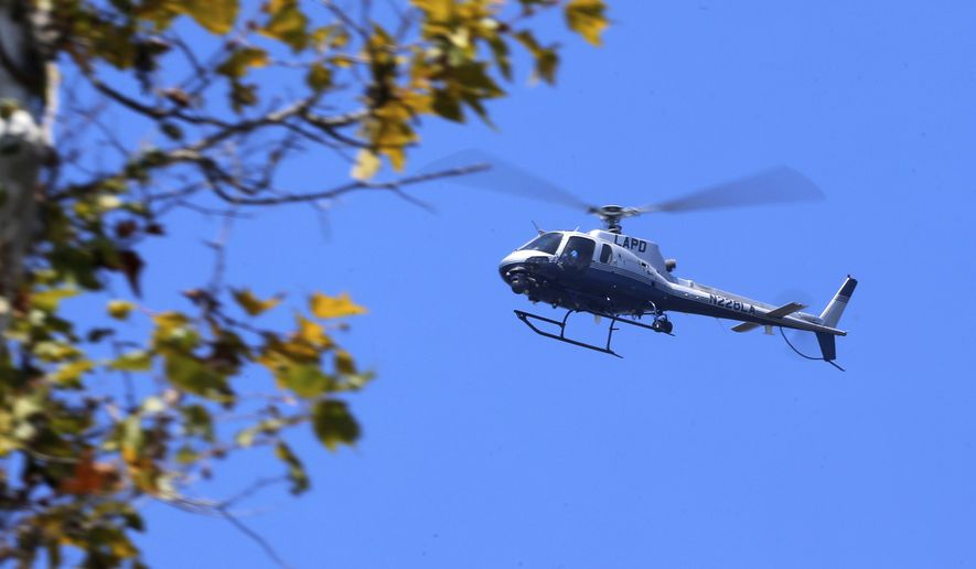 A Los Angeles Police helicopter flies above a home during a standoff in the upscale neighborhood in Pacific Palisades in Los Angeles Thursday, Aug. 10, 2017. (AP Photo/Damian Dovarganes)