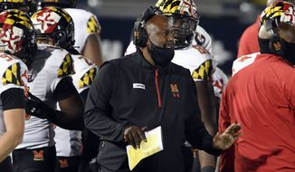 FILE - In this Saturday, Nov. 7, 2020, file photo, Maryland head coach Mike Locksley, center, talks with his players during a timeout late in the fourth quarter of an NCAA college football game against Penn State in State College, Pa. An outbreak of COVID-19 on the Maryland football team that resulted in a positive test for head coach Michael Locksley has caused the cancellation of Saturday's Big Ten game against Michigan State. (AP Photo/Barry Reeger, File)