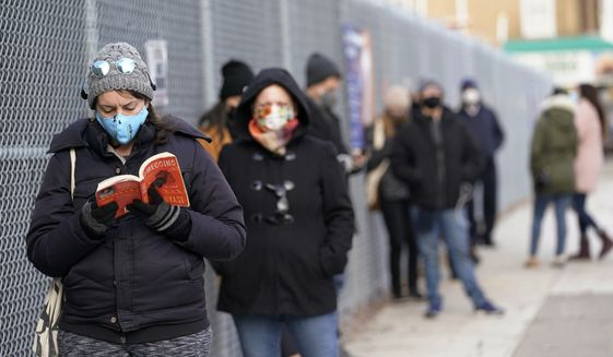 Ashley Gannon, left, reads a book as she and others wait in line outside a New York City Health + Hospitals COVID testing site in the Brooklyn borough of New York, Thursday, Nov. 19, 2020. Gannon says she gets tested periodically to make sure she is coronavirus-free. Some said they waited more than two hours to get a rapid test, one of two kinds of tests available at this particular site. Workers at the site said rapid test results take one to two days, while a regular test could take two to four days. At this testing site, there were longer lines for the rapid test as they are not available at all sites. (AP Photo/Kathy Willens)