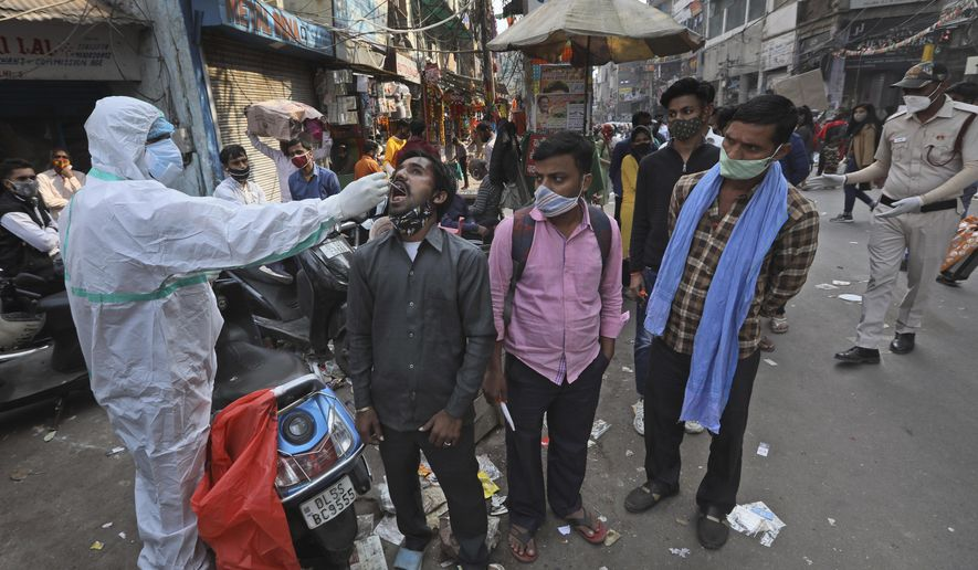 A health worker takes a sample to test for COVID-19 test at a market place in New Delhi, India, Thursday, Nov. 19, 2020. India's confirmed coronavirus caseload is expected to surpass 9 million on Friday as authorities in New Delhi battle to slow down the surge of infections in the city by increasing testing. The country's overall tally of confirmed cases is currently the second largest in the world behind the United States. (AP Photo/Manish Swarup)