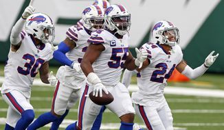 FILE - In this Oct. 25, 2020, file photo, Buffalo Bills defensive end Jerry Hughes (55) celebrates with teammates after an interception during an NFL football game against the New York Jets in East Rutherford, N.J. At 32, the Buffalo Bills defensive end might no longer be the angry young man of his youth, when his various on-field eruptions would intimidate opponents and teammates alike, and undisciplined personal fouls aggravate coaches. (AP Photo/Adam Hunger, File)