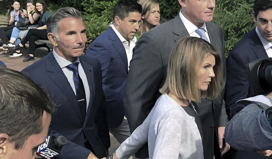 In this Aug. 27, 2019, file photo, Lori Loughlin departs federal court in Boston with her husband, Mossimo Giannulli, left, after a hearing in a nationwide college admissions bribery scandal. (AP Photo/Philip Marcelo, File)