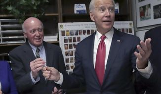 FILE— In this Nov. 8, 2019 file photograph, then Democratic presidential candidate former Vice President Joe Biden hands the pen to New Hampshire Secretary of State Bill Gardner, second from left, after filing to have his name listed on the New Hampshire primary ballot, in Concord, N.H. Gardner, the nation's longest serving secretary of state, is seeking a 23rd term in New Hampshire. (AP Photo/Charles Krupa)