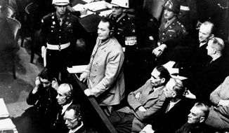 FILE - In this Nov. 21, 1945 file photo, Reichsmarshal Hermann Goering stands in the prisoner's dock at the Nuremberg War Crimes Trial in Germany. He is entering a plea of not guilty to the International Military Tribunal Indictment. Goering is wearing headphones of the court translating system. Germany marks the 75th anniversary of the landmark Nuremberg trials of several Nazi leaders and in what is now seen as the birthplace of a new era of international law on Friday, Nov. 20, 2020. (AP Photo, file)