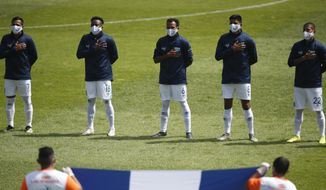 Players of the Guatemalan national soccer team sing their national anthem wearing face masks to prevent the spread of the new coronavirus, before a friendly soccer match against Honduras in Guatemala City, Sunday, Nov. 15, 2020. (AP Photo/Moises Castillo)