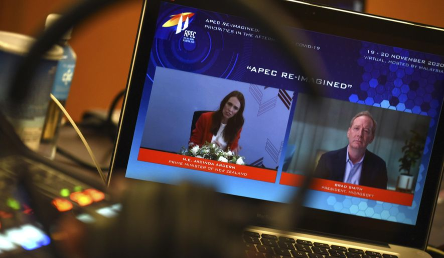 In this photo released by Malaysia Department of Information, a screen shows New Zealand's Prime Minister Jacinda Ardern, left, and Microsoft President Brad Smith speak via virtual meeting during the APEC CEO Dialogues 2020, ahead of the Asia-Pacific Economic Cooperation (APEC) leaders' summit in Kuala Lumpur, Malaysia, Friday, Nov. 20, 2020. (Fandy Azlan/Malaysia Department of Information via AP)