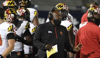 Maryland head coach Mike Locksley, center, talks with his players during a timeout late in the fourth quarter of an NCAA college football game in State College, Pa., Saturday, Nov. 7, 2020. (AP Photo/Barry Reeger)  **FILE**