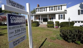 A real estate brokerage sign stands in front of a house, Tuesday, Oct. 6, 2020, in Norwood, Mass.  On Thursday, Nov. 19, U.S. long-term mortgage rates fell this week, reaching record lows for the 13th time this year amid fresh signs of weakness in the pandemic-ravaged economy.  (AP Photo/Steven Senne)