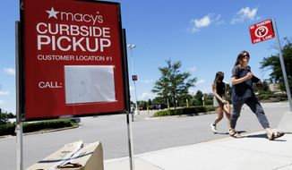 FILE - In this June 25, 2020 file photo, people walk past curbside pickup sign at Macy's department store in Vernon Hills, Ill. In the days before COVID-19, shopping smart used to mean scoring deals at a department store's weekend sale. But the pandemic has led to a shift in consumer habits. Now, many consumers are making their purchases online for home delivery or picking them up curbside. To save money while shopping during the pandemic, sign up for in-stock alerts, lean on your community, read reviews carefully and more.  (AP Photo/Nam Y. Huh, File)