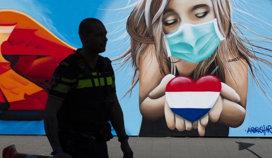A police officer is silhouetted as he passes a mural by artist Casper Cruse, showing a woman with a face mask holding a heart in the colors of the dutch flag in support for those suffering from the effects of the coronavirus, in The Hague, Netherlands. (AP Photo/Peter Dejong, FILE)