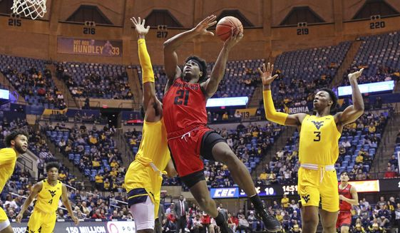Austin Peay guard Terry Taylor (21) drives to the basket as West Virginia forward Derek Culver, behind, and West Virginia forward Gabe Osabuohien (3) defend during the first half of an NCAA college basketball game in Morgantown, W.Va., in this Thursday, Dec. 12, 2019, file photo. Taylor, the reigning Ohio Valley Conference player of the year, averaged 21.8 points and 11 rebounds last season and is the first player in school history to score at least 500 points in three consecutive seasons. (AP Photo/Kathleen Batten, File)  **FILE**