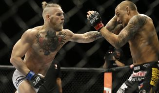 FILE - In this Sept. 27, 2014, file photo, Conor McGregor, left, and Dustin Poirier, exchange hits during their mixed martial arts bout in Las Vegas. UFC President Dana White confirmed to The Associated Press on Thursday, Nov. 19,2020, that McGregor has officially signed an agreement for a probable 155-pound fight with Poirier, ending McGregor's latest retirement from mixed martial arts. (AP Photo/John Locher, File)