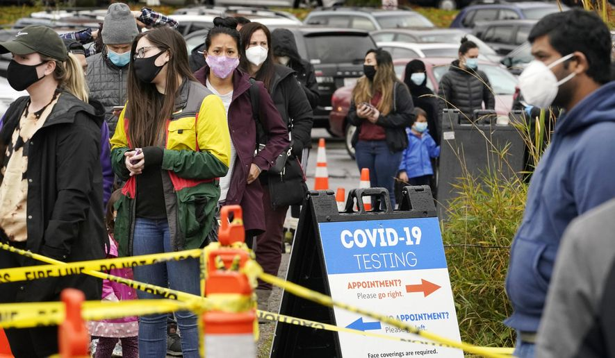 In this Nov. 18, 2020, file photo, people line up to be tested for the coronavirus at a free testing site in Seattle. With coronavirus cases surging and families hoping to gather safely for Thanksgiving, long lines to get tested have reappeared across the U.S. (AP Photo/Elaine Thompson, File)  **FILE**