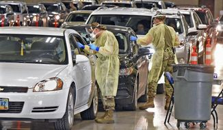 FILE - In this Nov. 17, 2020, file photo, North Dakota National Guard soldiers Spc. Samantha Crabbe, left, and Master Sgt. Melanie Vincent administer COVID-19 tests inside the Bismarck Events Center in Bismarck, N.D. With coronavirus cases surging and families hoping to gather safely for Thanksgiving, long lines to get tested have reappeared across the U.S. (Tom Stromme/The Bismarck Tribune via AP, File)