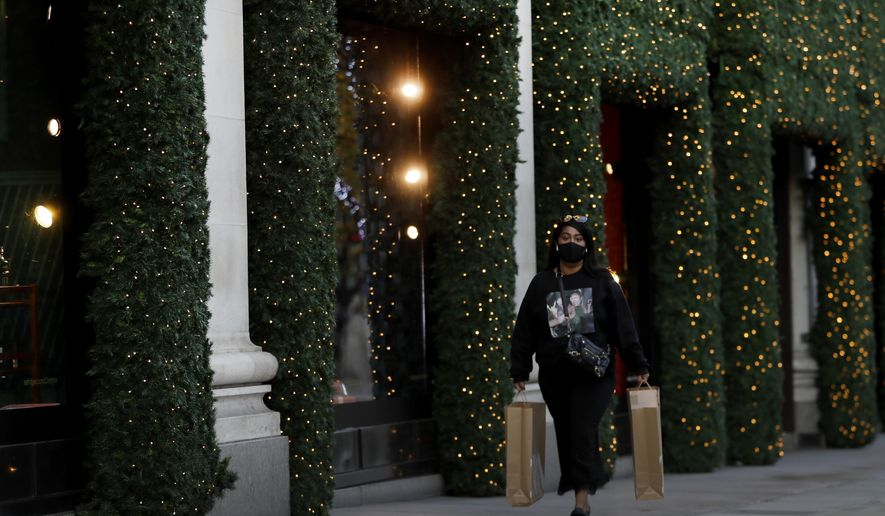 A woman walks past Christmas decorations on Oxford Street during a second lockdown in London, Thursday, Nov. 19, 2020. Businesses that have been forced to shut are hoping they will be able to reopen to salvage something of the crucial holiday shopping season. The government has been reluctant to say what restrictions will be in place for any particular area when the lockdown ends and says it's still too early to see how the lockdown has worked. (AP Photo/Kirsty Wigglesworth)