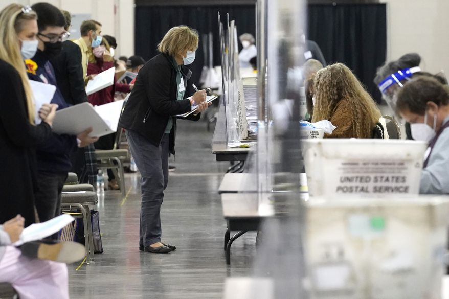 Recount observers watch ballots during a Milwaukee hand recount of Presidential votes at the Wisconsin Center, Friday, Nov. 20, 2020, in Milwaukee, Wis.  The recount of the presidential election in Wisconsins two most heavily Democratic counties began Friday with President Donald Trumps campaign seeking to discard tens of thousands of absentee ballots that it alleged should not have been counted.  (AP Photo/Nam Y. Huh)