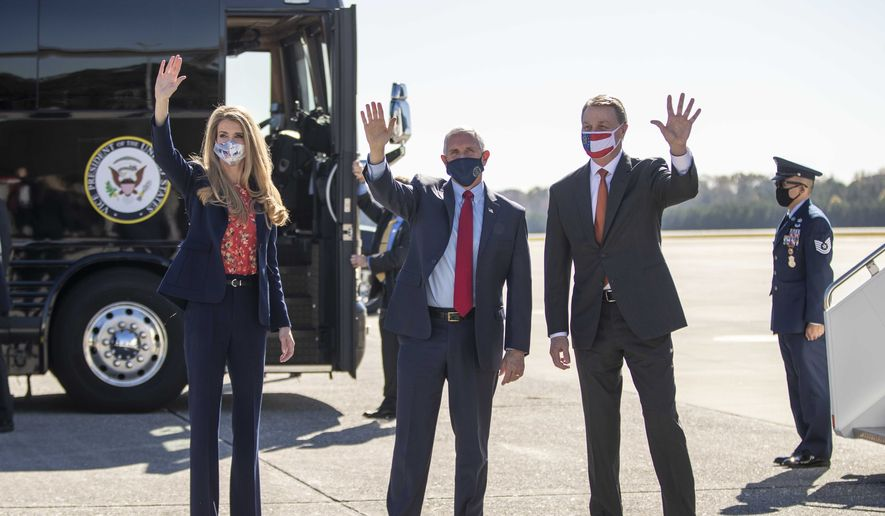 Vice President Mike Pence, center, Sen. Kelly Loeffler, left, and Sen. David Perdue, right, wave at individuals at Dobbins Air Reserve Base in Marietta, Ga., Friday, Nov. 20, 2020. Pence arrived on Friday to support Loeffler and Perdue, who are both facing a runoff election in January. (Alyssa Pointer/Atlanta Journal-Constitution via AP)