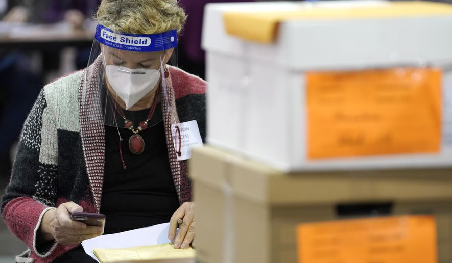 A election official works around ballots during a Milwaukee hand recount of Presidential votes at the Wisconsin Center, Friday, Nov. 20, 2020, in Milwaukee, Wis. The recount of the presidential election in Wisconsin's two most heavily Democratic counties began Friday with President Donald Trump's campaign seeking to discard tens of thousands of absentee ballots that it alleged should not have been counted. (AP Photo/Nam Y. Huh)