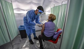 A person receives a flu vaccine shot in a tent set up next to Duomo Cathedral in downtown Milan, Italy, Friday, Nov. 20. Health authorities are advising elderly people to vaccine against flu, and offering free vaccination to over 65, also in a tentative to avoid possible confusion with some symptoms of COVID-19, that could mislead diagnosis. The tent was set up to help avoiding eccessive clogging in hospitals. (Claudio Furlan/LaPresse via AP)