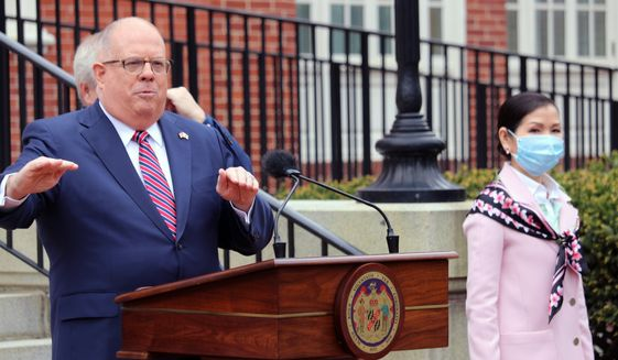 In this Monday, April 20, 2020  file photo, Maryland Gov. Larry Hogan speaks at a news conference in Annapolis, Md., with his wife, Yumi Hogan, right, where the governor announced Maryland has received a shipment from a South Korean company to boost the state's ability to conduct tests for COVID-19 by 500,000. Maryland lawmakers are renewing criticism of Gov. Larry Hogan's procurement of 500,000 COVID-19 tests from South Korea after The Washington Post reported the first batch was flawed and never used, Friday, Nov. 20, 2020. (AP Photo/Brian Witte, File)  **FILE**