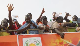 Supporters of Burkina Faso President Roch Kabore attend a campaign rally in Bobo-Dioulasso Thursday, Nov. 5, 2020. Burkina Faso will go to the polls on Nov. 22, 2020, to vote in presidential and legislative elections marred by ongoing violence. Attacks linked to Islamic militants have ravaged the once peaceful nation.(AP Photo/Sam Mednick)