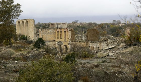 """A view of a vast expanse of jagged concrete and houses reduced to shells in Agdam, prior to the Azerbaijani forces being handed control in the separatist region of Nagorno-Karabakh, Thursday, Nov. 19, 2020. Although regaining Agdam is a triumph for Azerbaijan, the joy of returning is shot through with grief and anger. What was once a notably pleasing city of 50,000 known for its white homes and an elaborate three-story teahouse is so ruined that it's sometimes called the """"Hiroshima of the Caucasus."""" (AP Photo/Sergei Grits)"""
